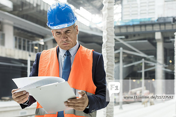 Businessman reviewing paperwork on clipboard at construction site