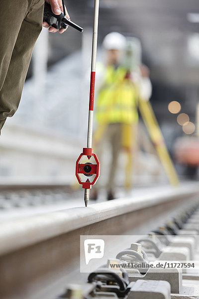 Engineers surveying tracks at construction site