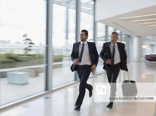 Geschäftsleute  die mit dem Koffer auf dem Flughafen rennen.