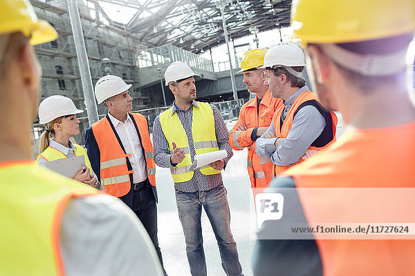 Foreman  engineers and construction workers meeting at construction site