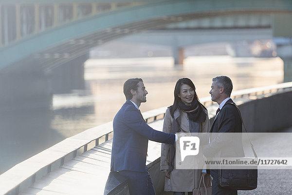 Geschäftsleute beim Händeschütteln am städtischen Ufer