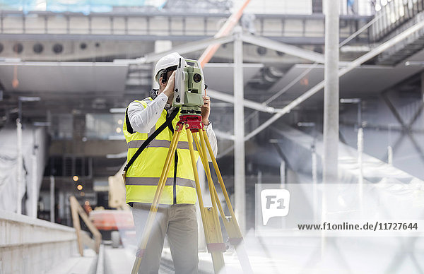 Male engineer using theodolite at construction site