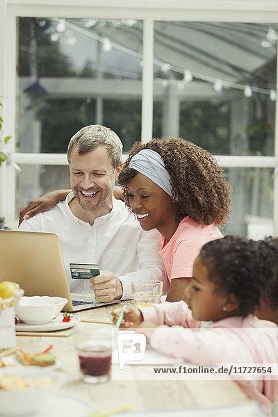 Multi-ethnische junge Familie online einkaufen mit Kreditkarte am Laptop
