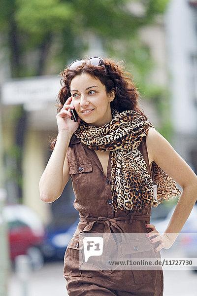 Frau auf dem Handy lächelnd und spazierend in der Stadt