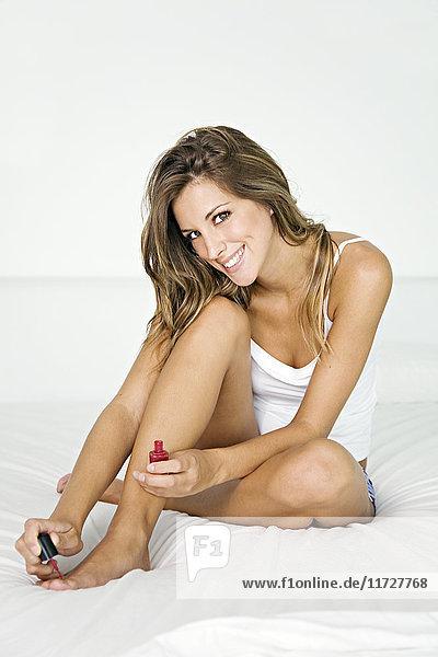 Blonde Frau bemalt ihre Nägel im Bett