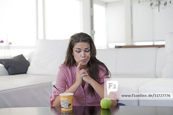 Junge Frau  die versucht ist  sich gesund oder ungesund zu ernähren.