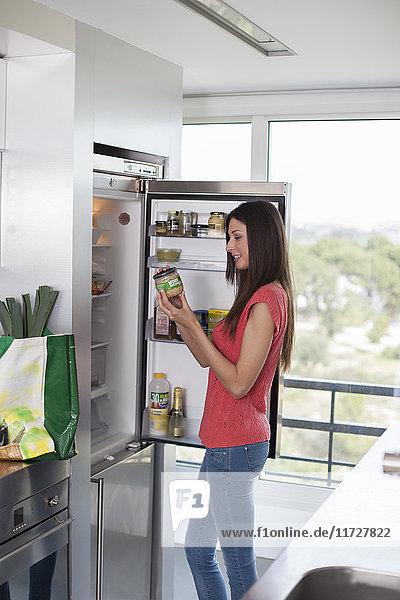 Frau am Kühlschrank beim Lesen von Zutaten auf einem Topf