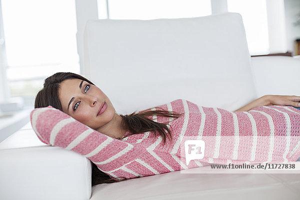 Entspannte brünette Frau auf dem Sofa liegend,  tagträumend