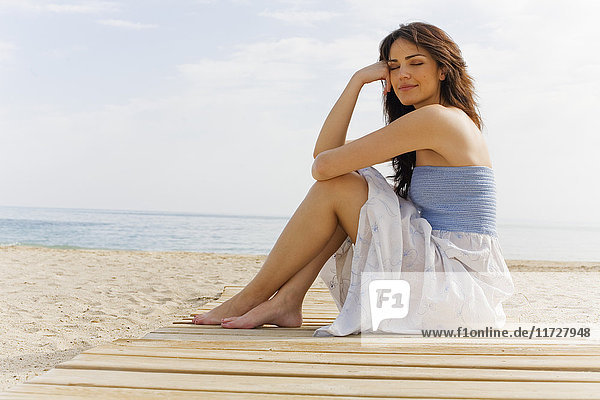 Porträt einer schönen brünetten Frau  die am Strand sitzt