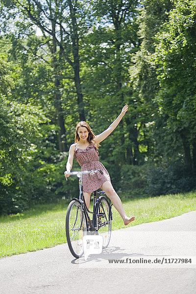 Hübsche Frau mit Fahrrad im Park