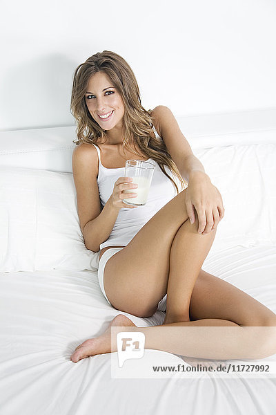 Blonde Frau beim Frühstück auf dem Bett sitzend