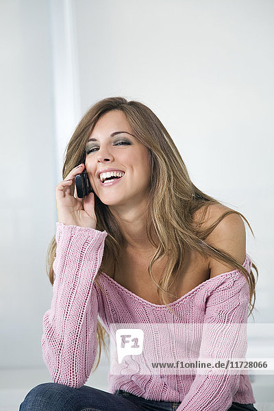 Portrait of a beautiful blonde woman talking on the phone and smiling