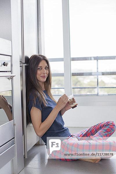 Schöne Frau beim Schokoladenessen zu Hause