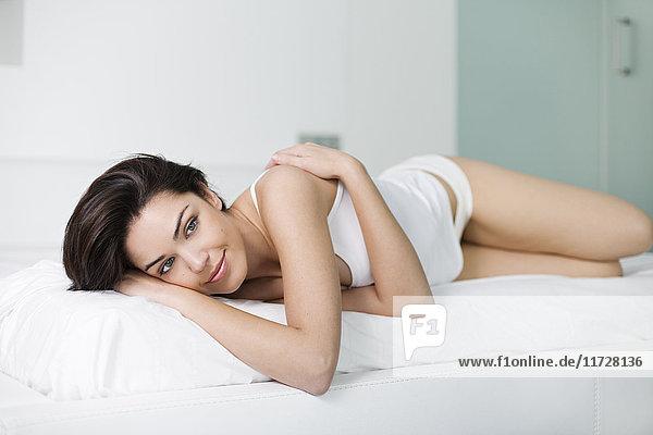 Porträt einer hübschen nachdenklichen Frau im Bett