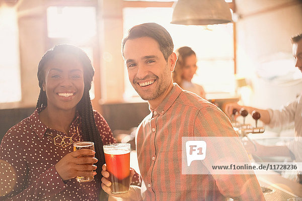 Portrait smiling couple drinking beer in bar