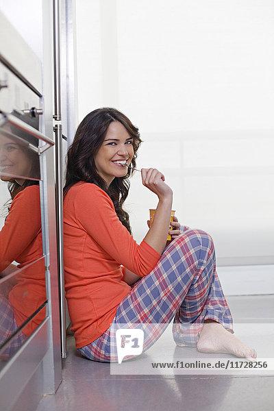 Hübsche brünette Frau genießt ein Eis in der Küche
