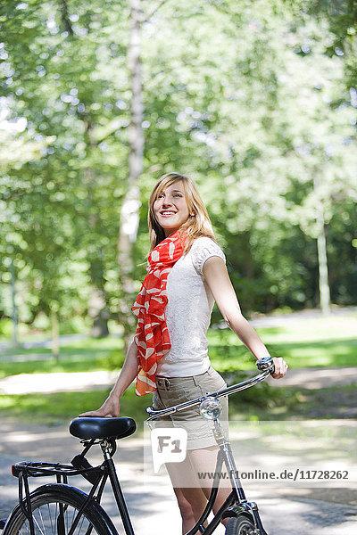 Hübsche blonde Frau mit Fahrrad im Park