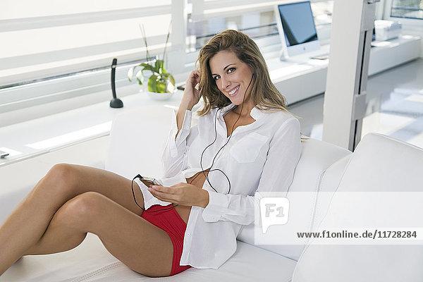 Porträt einer schönen und sinnlichen Frau auf der Couch beim Musikhören