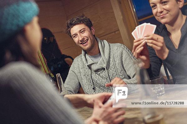 Freunde spielen Karten am Tisch in der Kabine