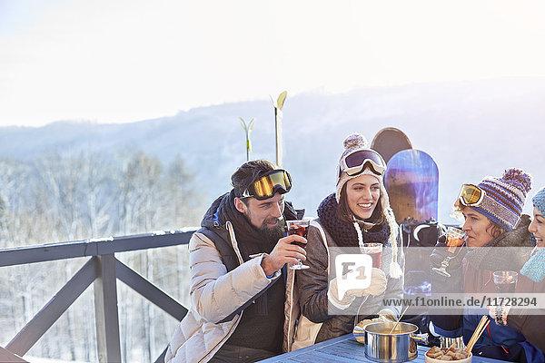 Snowboarder und Skifahrerfreunde trinken Cocktails auf dem Balkon Apres-Ski