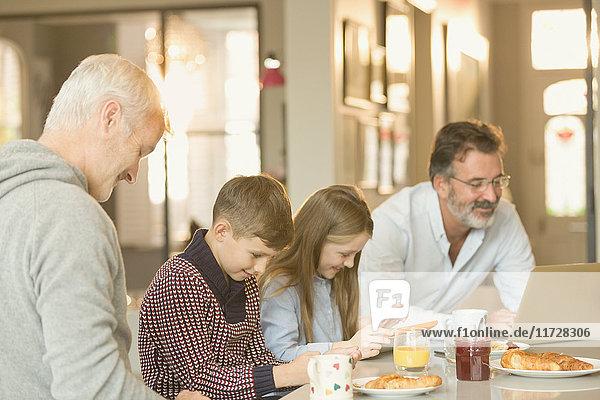 Männliche schwule Eltern und Kinder beim Frühstücken und mit Laptop und digitalem Tablett am Küchenarbeitsplatz
