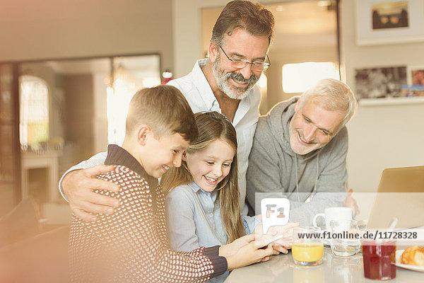 Männliche schwule Eltern und Kinder  die ihr Handy an der Küchenzeile benutzen.