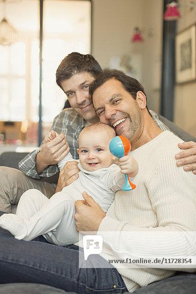 Portrait männliche schwule Eltern und kleiner Sohn mit Rassel