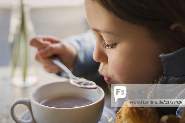 Nahaufnahme Mädchen bläst auf heiße Suppe