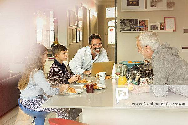 Männliche schwule Eltern und Kinder beim Frühstück an der Küchentheke