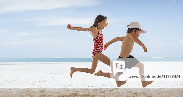 Boy and girl brother and sister running on tropical beach