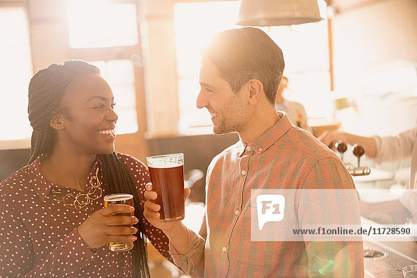 Smiling couple drinking beer in bar