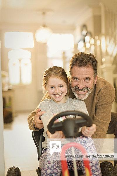 Porträt lächelnder Vater und Tochter beim Spielen mit dem Spielzeugauto