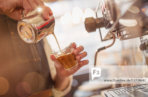 Close up barista pouring milk into espresso at espresso machine in cafe