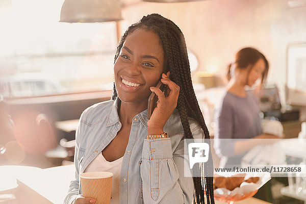 Smiling woman talking on cell phone and drinking coffee in cafe