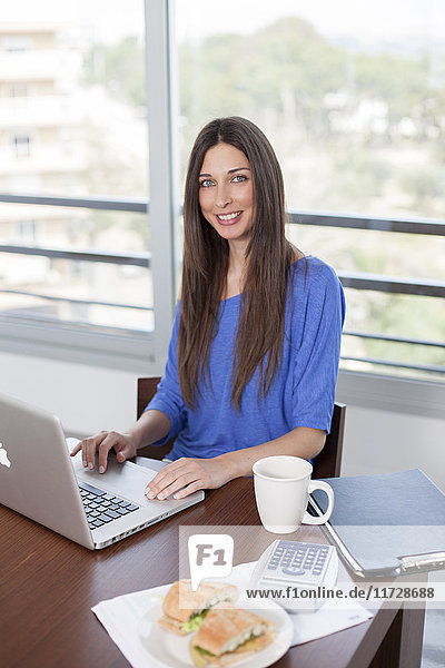 Brunette woman with laptop and sandwich at home