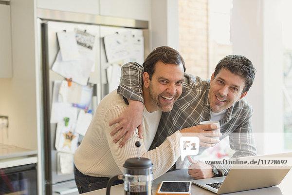Portrait liebevolle männliche Homosexuell Paar trinken Kaffee und mit Laptop in der Küche