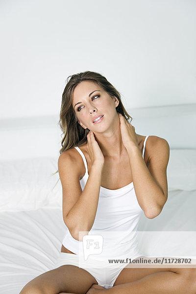 Frau streckt sich mit Rückenschmerzen im Bett