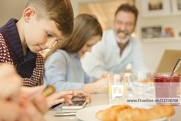 Junge mit Handy am Frühstückstisch