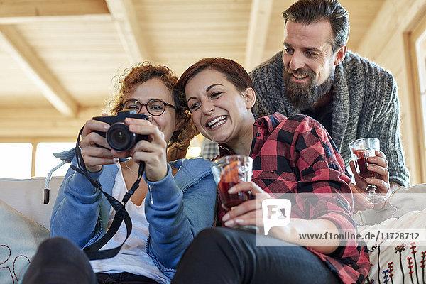Freunde beim Betrachten von Fotos auf der Digitalkamera und beim Trinken von heißem Toddy in der Kabine