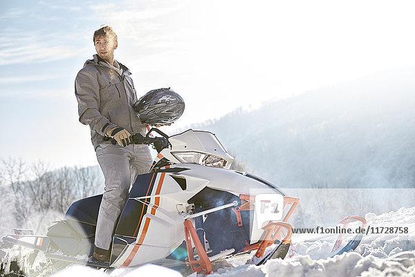 Mann fährt Schneemobil im sonnigen Schneefeld