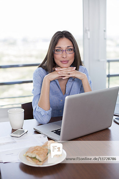 Pretty brunette woman with laptop and sandwich smiling at camera