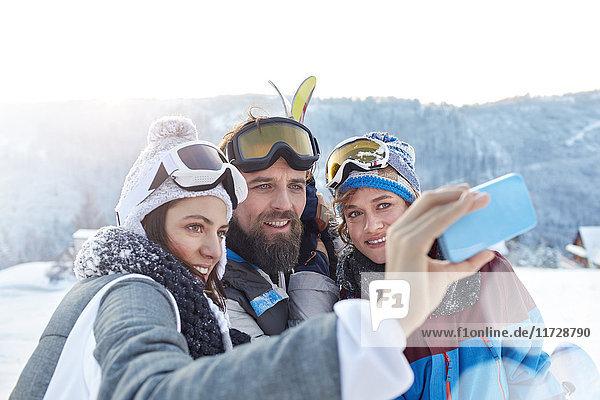 Skifahrerfreunde nehmen Selfie mit Fotohandy im Schneefeld mit