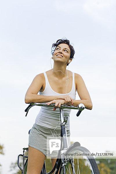 Porträt einer brünetten Frau beim Radfahren im Park