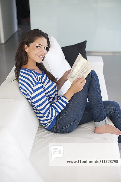Brunette woman reading a book at the sofa