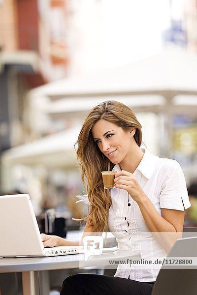 Woman with laptop having a coffee outdoor