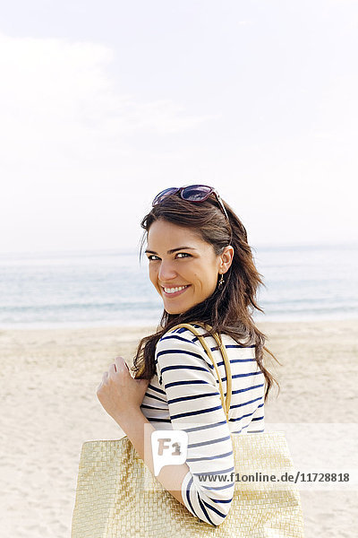 Porträt einer jungen brünetten Frau,  die am Strand ankommt