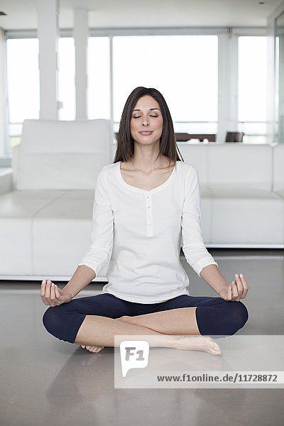 Healthy young woman doing yoga at home