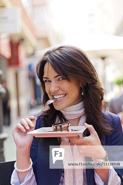 Frau genießt einen Schokoladenkuchen in einem Cafe