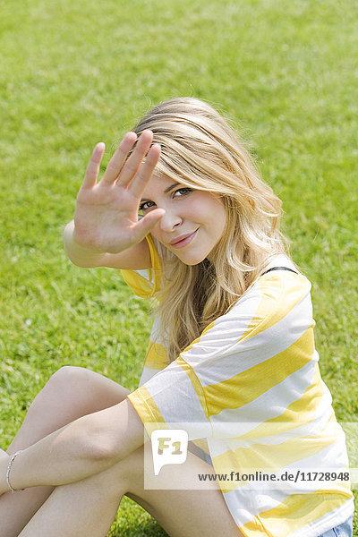 Junge blonde Frau genießt einen Tag im Park und versteckt sich mit der Hand.