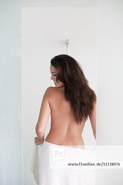 Rückansicht einer brünetten jungen Frau beim Duschen